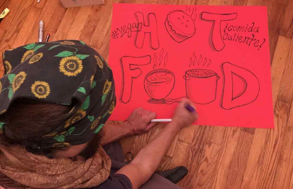 Phillip Gladkov making signs for the Community Solidarity Vegan Thanksgiving